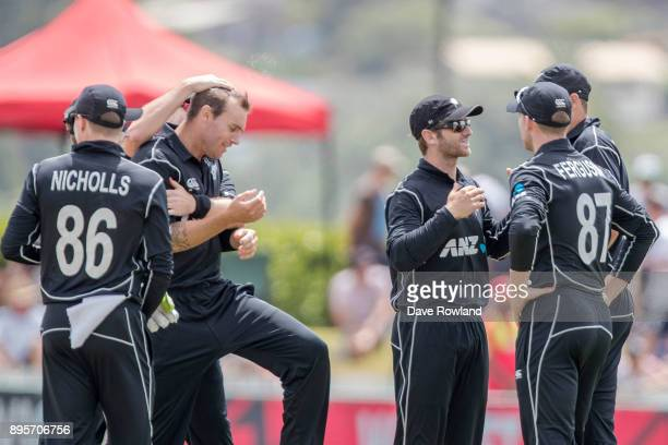 New Zealand congratulate bowler Doug Bracewell for taking the wicket of Chris Gayle of West Indies during the first match in the One Day...