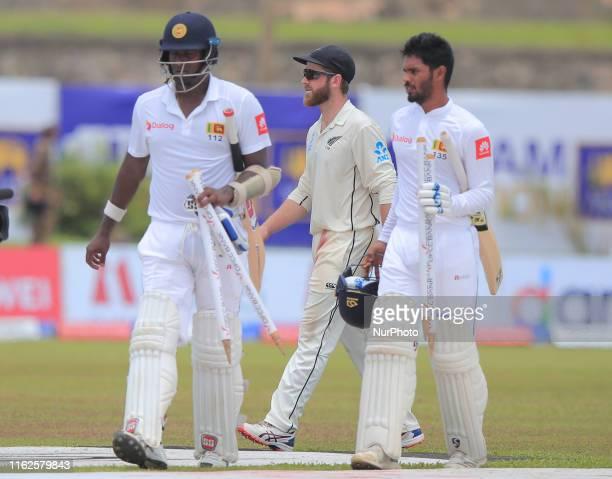 New Zealand cricket captain Kane Williamson Sri Lankan cricketer Angelo Mathews and Dhananjaya de Silva walks back after the fifth day's play of the...
