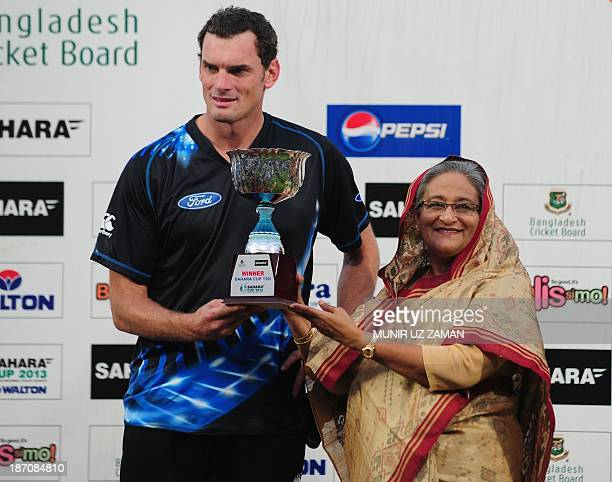 New Zealand cricket captain Kyle Mills receives the T20 trophy from the Bangladesh Prime Minister Shiekh Hasina Wajed after winning the T20 cricket...
