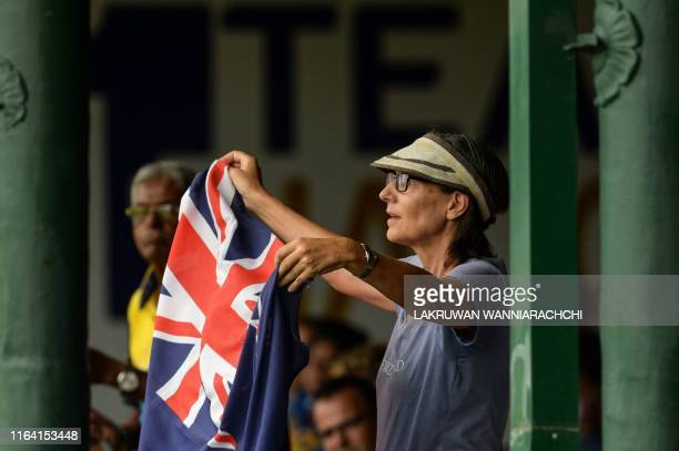 A New Zealand cricket fan holds a national flag as she cheers up during the final day of the final cricket Test match between Sri Lanka and New...