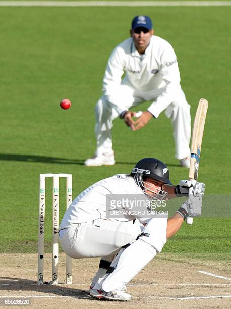 New Zealand cricketer Daniel Flynn ducks the ball as Indian feilder VVS Laxman looks on during the third day of the first Test match between India...