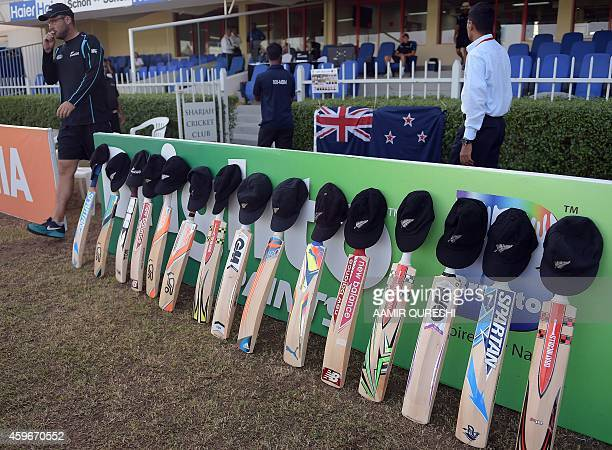 New Zealand cricketer Daniel Vettori walks past bats and caps placed outside the New Zealand dressing room to match the campaign #putoutyourbats'...