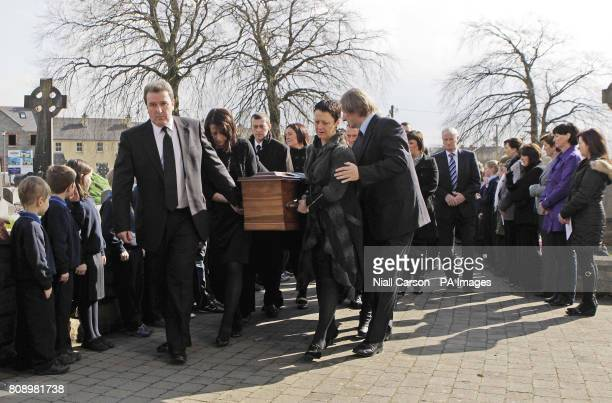 New Zealand earthquake victim Owen McKenna's sisters Bernadette and Catherine carry his coffin in to the grounds of Church of the Sacred Heart...