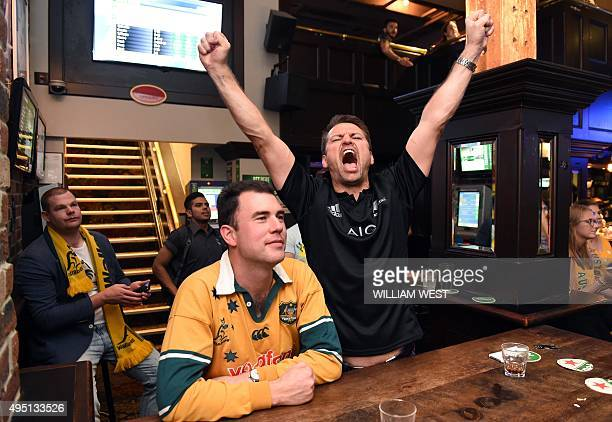 A New Zealand fan celebrates on November 1 as he watches the New Zealand All Blacks defeat the Australian Wallabies on a big screen in a Sydney...