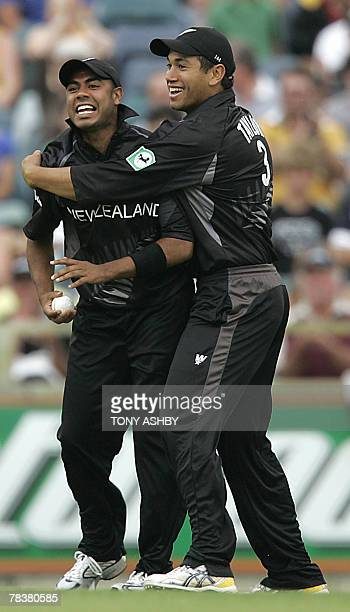 New Zealand fieldsman Jeetan Patel is congratulated by Ross Taylor after catching Australian opening batsman Adam Gilchrist for one run off the...