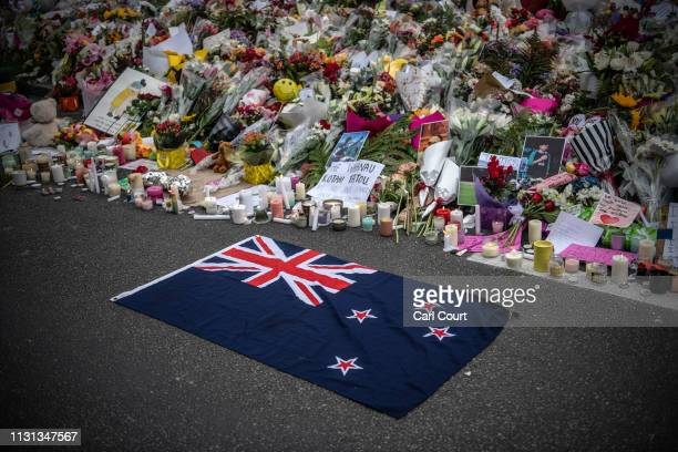 New Zealand flag is placed next to flowers and tributes near Al Noor mosque on March 18 2019 in Christchurch New Zealand 50 people were killed and...