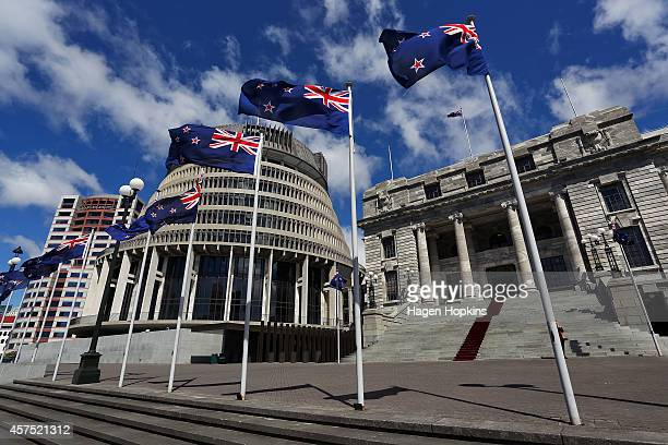 New Zealand flags fly in front of The Beehive and Parliament House during the Commission Opening of Parliament on October 20, 2014 in Wellington, New...