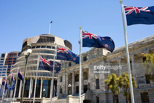 New Zealand flags flying in front of the Beehive and New Zealand's Parliament House.