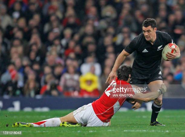New Zealand fly half Dan Carter is tackled by Welsh centre James Hook during the Autumn International rugby union match between Wales and New Zealand...
