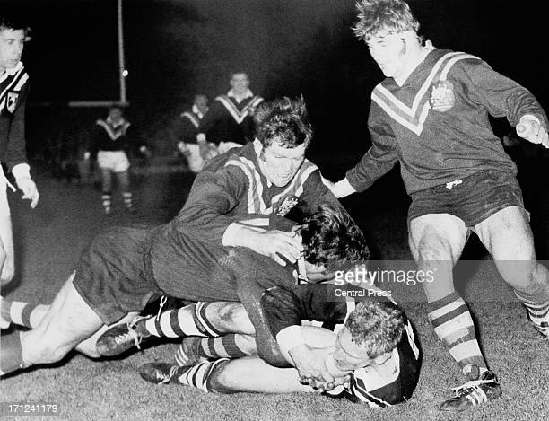 New Zealand front row forward Gary Smith is brought down by Australia's Bob McCarthy and Elwyn Walters during Australia's first match in defence of...