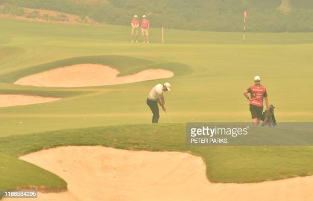 TOPSHOT New Zealand golfer Ryan Chisnall hits a shot on the fairway through thick haze from bushfires at the 1st hole on day one of the Australian...
