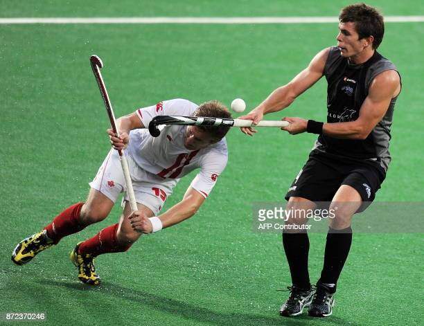 New Zealand hockey player Nick Haig vies for the ball with Canadian hockey player Mark Pearson during their World Cup 2010 match at the Major Dhyan...