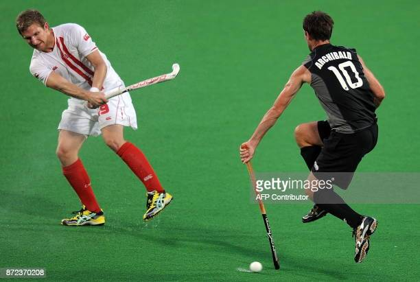 New Zealand hockey player Ryan Archibald blocks a stroke by Canadian hockey player Mark Pearson during their World Cup 2010 match at the Major Dhyan...