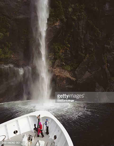 new zealand, milford sound, two girls (9-11) on tour boat - blasius erlinger stock pictures, royalty-free photos & images
