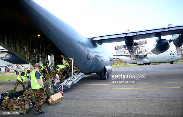 New Zealand military personnel offload relief supplies for areas hit by Cyclone Pam from a plane at the airport on the Vanuatu island of Tanna on...