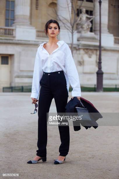 New Zealand model Georgia Fowler wears a white Balenciaga shirt with an open collar black pants and a black Celine bag after the Elie Saab show at...