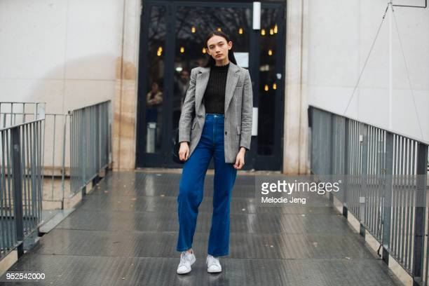 New Zealand model Natarsha Orsman wears a gray plaid blazer black sweater blue jeans and white sneakers on March 04 2018 in Paris France
