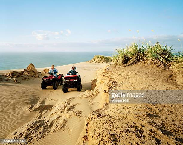 new zealand, ninety mile beach, couple quadbiking - northland new zealand stock pictures, royalty-free photos & images