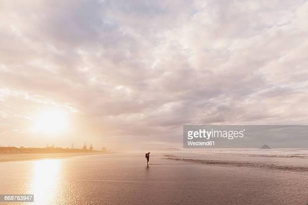 New Zealand, North Island, Bay of Plenty, Ohope Beach, man watching ocean waves, South Pacific Ocean
