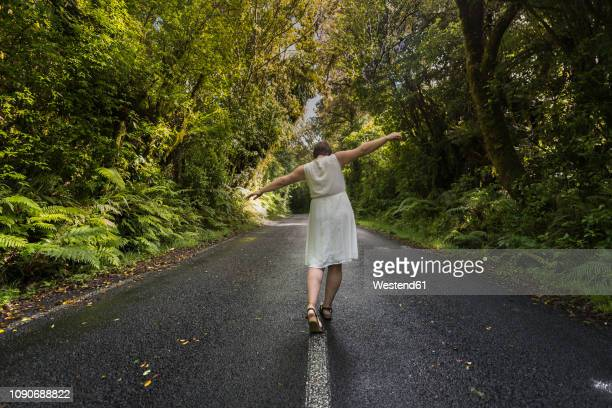 New Zealand, North Island, Egmont National Park, Woman balancing on centre line on road