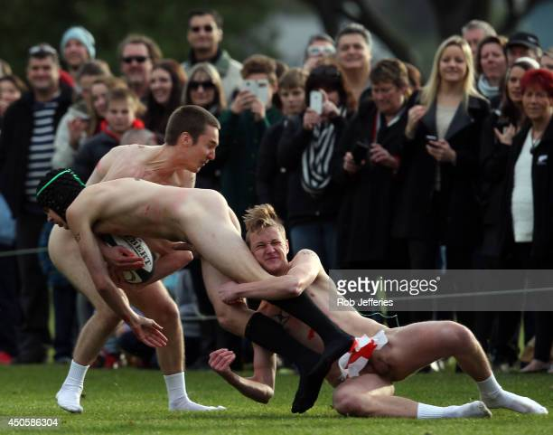 A New Zealand Nude Blacks players is tackled by England players during the Naked Rugby match between New Zealand and England at University Oval on...