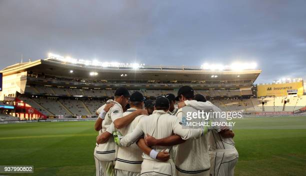 New Zealand players have a team huddle as they walk onto the field for the last session on the fifth day of the day-night cricket test match between...