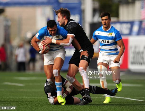 New Zealand players Tim Mikkelson right and Sherwin Stowers ground tackle Argentina player Lucas Belloto during their sevens rugby match during the...