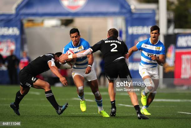 New Zealand players Tim Mikkelson right and Sherwin Stowers left tackle Argentina player Lucas Belloto during their sevens rugby match during the...