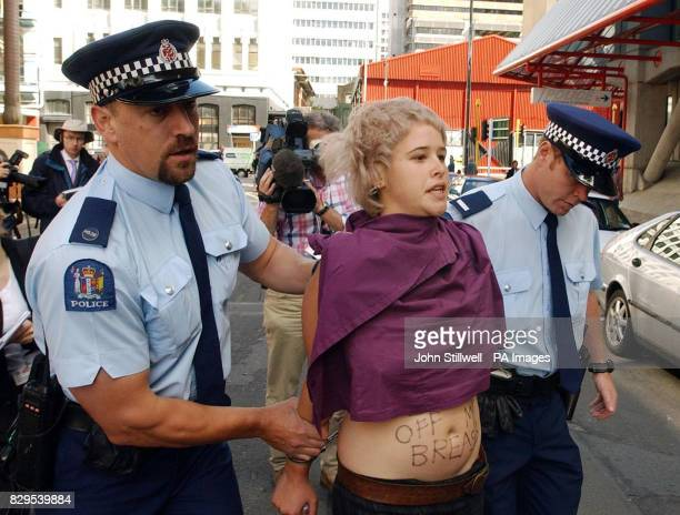 New Zealand Police officers remove Hannah Plant after she and another woman were taken to Wellington police Headquarters after allegedly flashing...