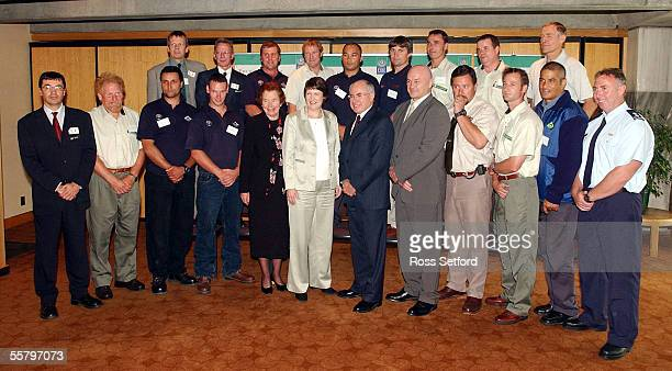 New Zealand Prime Minister Helen Clark and Australian Prime Minister John Howard centre pose with fire fighters who had helped in the Australian bush...