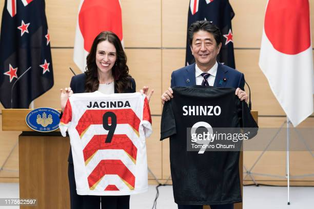 New Zealand Prime Minister Jacinda Ardern and Japan's Prime Minister Shinzo Abe hold jerseys bearing their names after a joint press conference on...
