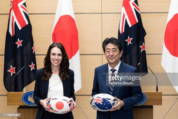New Zealand Prime Minister Jacinda Ardern and Japan's Prime Minister Shinzo Abe hold rugby balls after a joint press conference on September 19 2019...