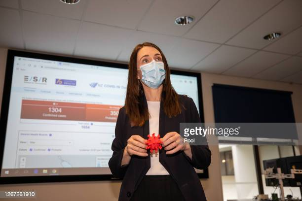 New Zealand Prime Minister Jacinda Ardern holds a 3D model of COVID-19 during a tour of the Institute of Environmental Science and Research on August...