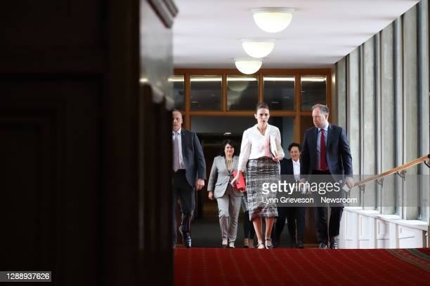 New Zealand Prime Minister Jacinda Ardern walks with press secretary Andrew Campbell down a corridor in New Zealand's Parliament on her way to the...