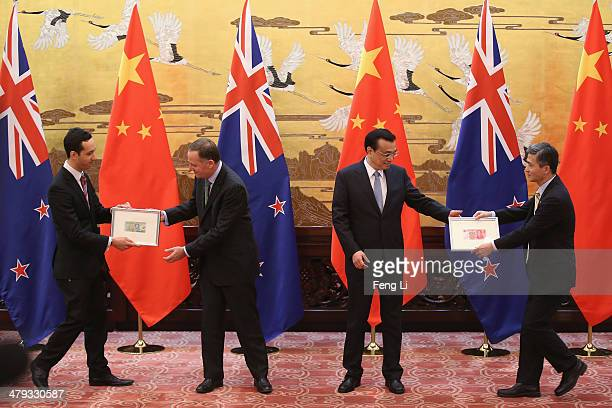 New Zealand Prime Minister John Key and Chinese Premier Li Keqiang change Chinese Yuan and New Zealand Dollar banknotes during an announcement...