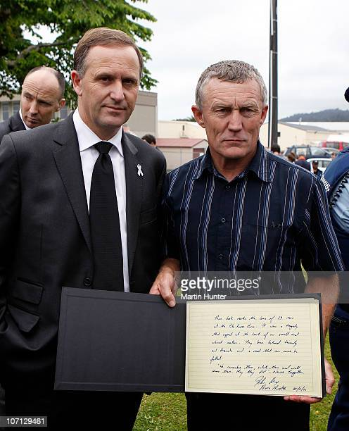 New Zealand Prime Minister John Key and Greymouth Mayor Tony Kokshoorn pose with a condolence book during a visit to Greymouth to meet with families...