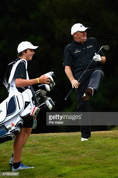 New Zealand Prime Minister John Key reacts on the 13th hole as his ball lands in the public gallery as his son and caddy Max Key looks on during...