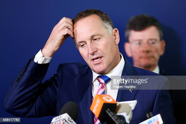 New Zealand Prime Minister John Key speaks to media while GCSB and NZ Security and Intelligence Minister Christopher Finlayson looks on after...