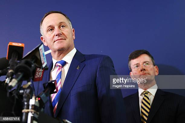 New Zealand Prime Minister John Key speaks to media while National MP and GCSB and NZ Security and Intelligence Minister Christopher Finlayson looks...