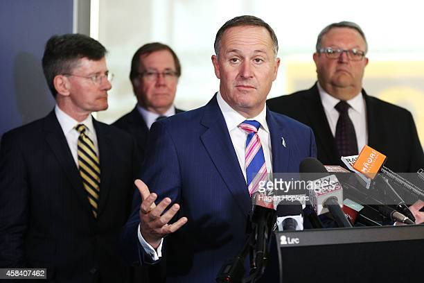 New Zealand Prime Minister John Key speaks to media while National MPs Chris Finlayson Murray McCully and Gerry Brownlee look on after delivering a...