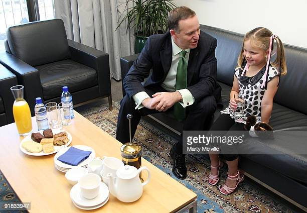 New Zealand Prime Minister John Key takes afternoon tea with 6 yearold Breanna Newman winner of the Phones for Starship competition at The Beehive on...