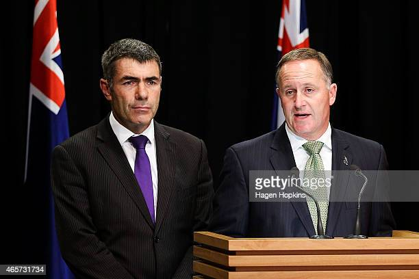 New Zealand Prime Minister John Key talks to the media while Minister for Primary Industries Nathan Guy looks on at Parliament House on March 10 2015...