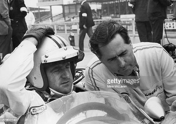 New Zealand racing driver Denny Hulme confers with his team mate Australian racing driver Jack Brabham before a practice run for the British Grand...