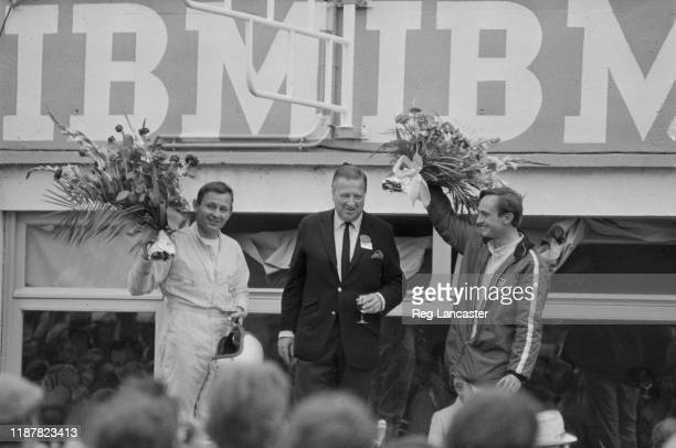 New Zealand racing drivers Bruce McLaren and Chris Amon with Ford CEO Henry Ford II on the podium after winning the 24 Hours of Le Mans, the 34th...