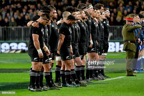 New Zealand rugby players stand for a moments silence to honour the passing of All Black great Colin Meads during the second Bledisloe Cup match...