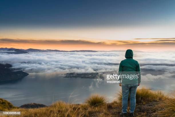 new zealand, south island, wanaka, otago, woman on coromandel peak at sunrise - look back at early colour photography stock photos and pictures