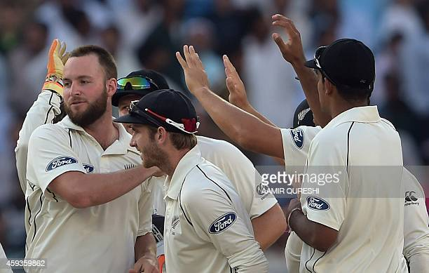 New Zealand spinner Mark Craig celebrates with teammates after taking the wicket of Pakistani batsman Younis Khan during the fifth and final day of...