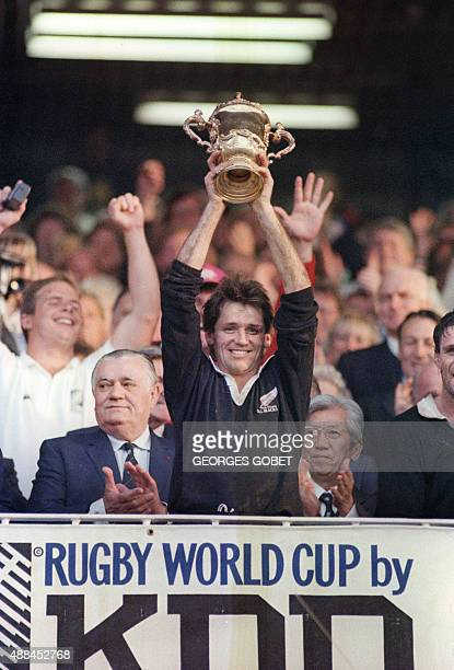 New Zealand team captain and scrumhalf David Kirk raises the Webb Ellis cup 20 June 1987 at Eden Park in Auckland after his team's victory over...