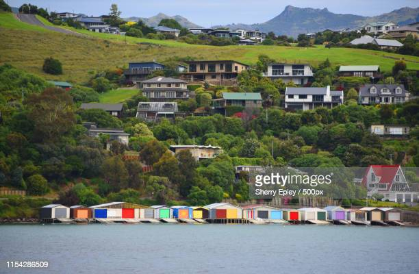 new zealand- view of the colorful akaroa boat houses - christchurch nieuw zeeland stockfoto's en -beelden