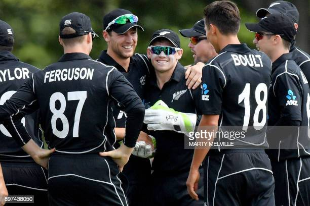 New Zealand wicketkeeper Tom Latham celebrates with teammates after catching a ball off the bat of West Indies batsman Shai Hope during the second...